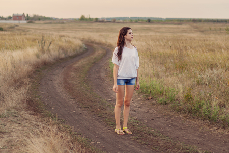 stays: Young girl with long brown hair stays at the road in autumn field. Selective focus, warm tinted. Stock Photo