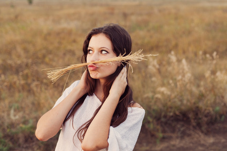Young girl with long brown hair making a mustache with a spikelets at the autumn field. Selective focus, warm tinted.