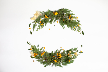 Christmas concept - frame wreath with evergreen Cupressus nootkatensis and Pyracantha red and yellow berries. Flat lay, top view.