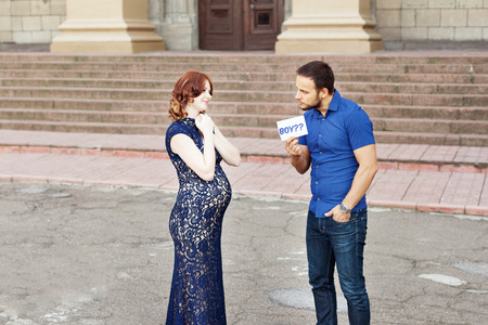 natural childbirth: Funny image. Couple expecting a baby: man holds a sign saying boy? Pregnancy in long dress. Future daddy in jeans and blue shirt.