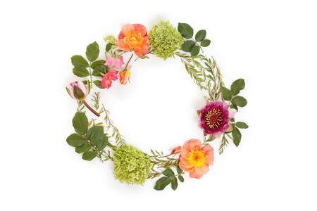 Couronne ronde florale (couronne) avec des fleurs et des feuilles. Flat lay, vue de dessus. Arrangement créatif avec des roses roses et oranges, des feuilles grises de grefsheim (spiraea cinerea), du septbark (hydrangea arborescens) et du nymphéa nymphaea.
