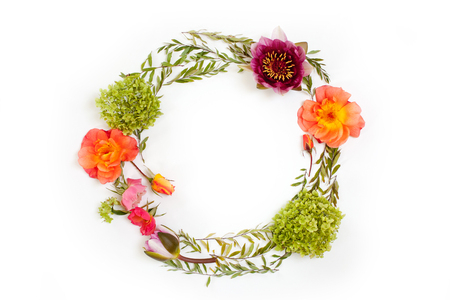 Floral round crown (wreath) with flowers and leaves. Flat lay, top view. Creative arrangement with pink and orange roses, gray grefsheim (spiraea cinerea) leaves, sevenbark (hydrangea arborescens) and nymphaea waterlily.