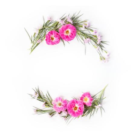 Plat leggen frame krans met anjer en roze bloemen en groene bladeren op wit. Bovenaanzicht vakantie concept. Stockfoto