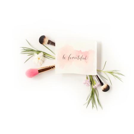 Hoogste mening van kosmetische borstels met groene die bladeren en bloemen en inspirational woorden in kalligrafiestijl `worden geschreven` Mooi op wit zijn. Schoonheid blog plat lag concept.