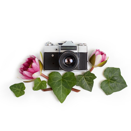 Vintage retro photo camera, dogwood green leaves (cornus alba) and nymphaea waterlily purple flowers on white background. flat lay, top view.