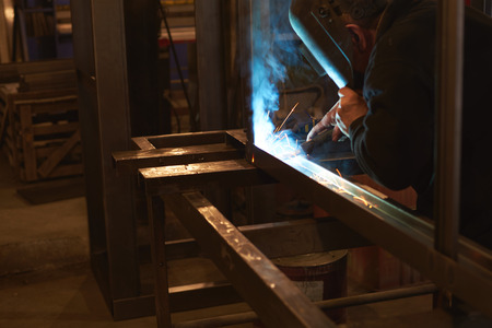 welder welds a metal frame for the power plant. The man works in a protective mask.