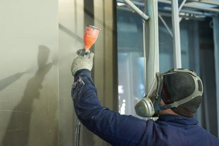 Un uomo produce prodotti in metallo con vernice a polvere. Un uomo lavora con una maschera.