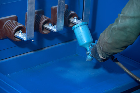 Man paints with blue paint with metal products spray gun. Painting of transformer substation. Stock Photo