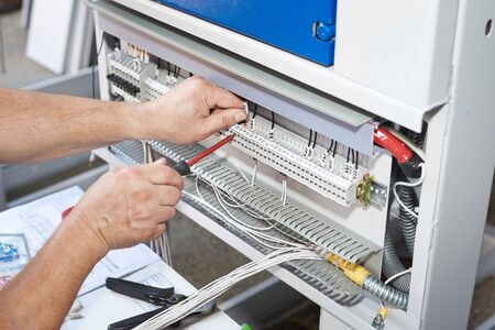 The electrician performs the installation and configuration of high-voltage equipment. High level master.