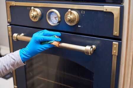 Girl washes the working surface of the gas stove with a sponge and detergent. General cleaning.