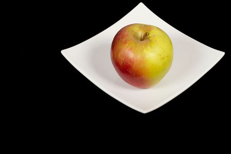 Apple on plate isolated on the black background photo