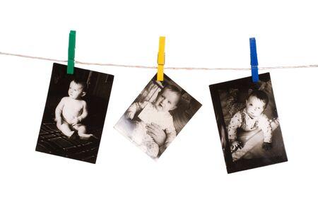 adjuntar: Vieja foto con beb� adjuntar a la clavija de color de ropa de cuerda sobre fondo blanco  Foto de archivo