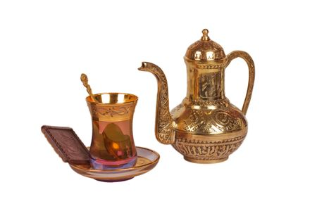Oriental cup with tea, spoon and kettle
