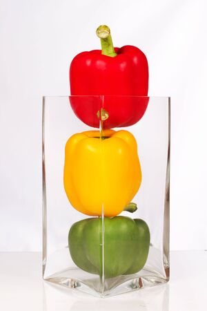 Fresh and delicious stoplight bell peppers in vase Stock Photo