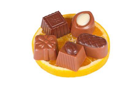 Delicious close up of chocolate candy on orange slice, isolated on white background Stock Photo