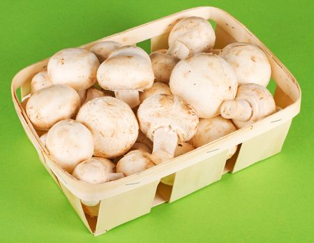 Fresh appetizing mushrooms in a basket on a green background.