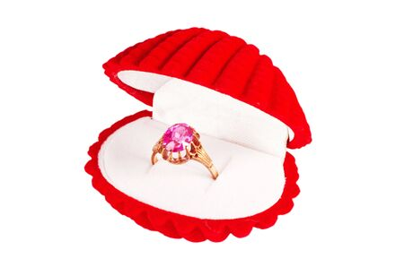 A red seashell box with golden ring