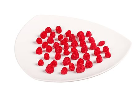Many fresh red raspberry on plate, isolated in white
