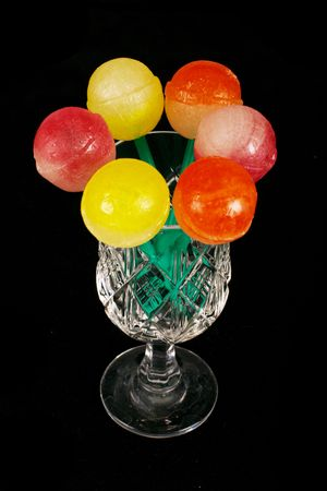 Colorful sweet lollipops in the glass on the black background Stock Photo
