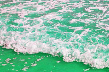 Green sea foam on sand Stock Photo