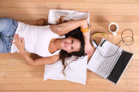 taking charge: A girl laying on the Floor after surfing on the Internet with a Laptop