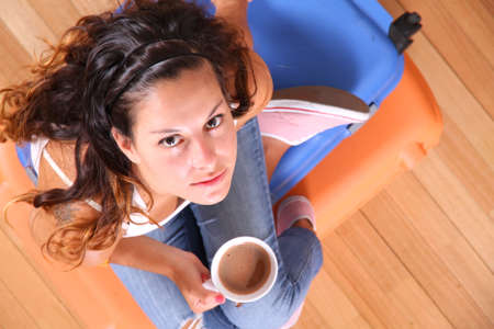 A young woman sitting on a stack of suitcases while drinking coffee and waiting for the departure to vacations  photo