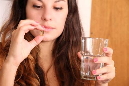 personas tomando agua: Una mujer joven que toma una píldora con un vaso de agua