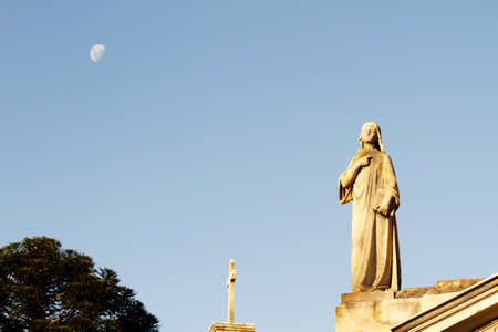 Statue in the Cemetery of Recoleta with the Moon in the background, Buenos Aires, Argentina  photo