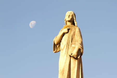 angel headstone: Statue in the Cemetery of Recoleta with the Moon in the background, Buenos Aires, Argentina