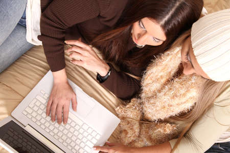 Two girls planning their winter holidays online Stock Photo - 13741146
