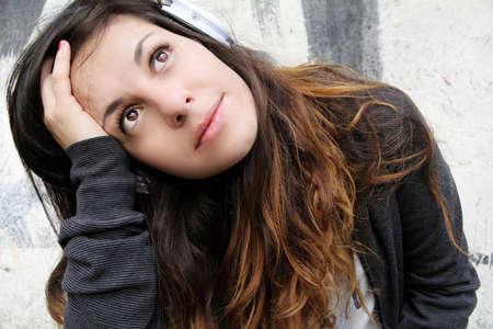 melancholijny: Młoda kobieta słuchania muzyki melancholijnej i siedząc na chodniku