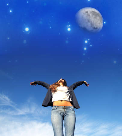 eclipse: A young woman jumping to the night sky