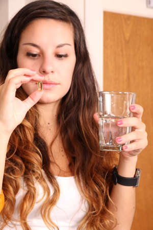 A young woman taking a pill with a glass of water  Stock Photo
