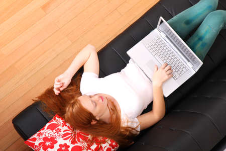 A young woman surfing on the Internet with a Laptop    photo