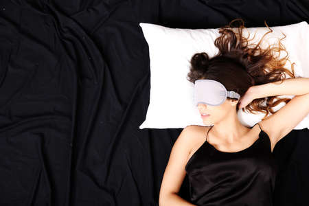 A young woman sleeping with a eye covering mask