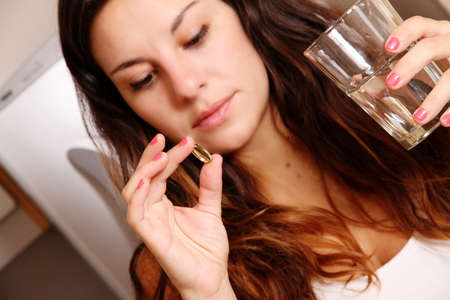 A young woman taking a pill with a glass of water  photo