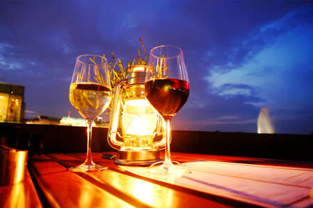 A glass of red and white wine besides a lantern
