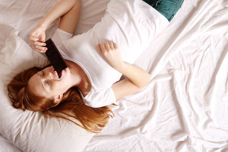A young redhead woman eating Chocolate in Bed
