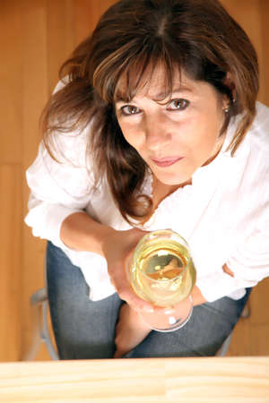 A beautiful mature woman with a glass of white wine  photo