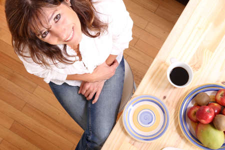 Portrait of a beautiful mature woman sitting in the kitchen  Focus on the Table  photo