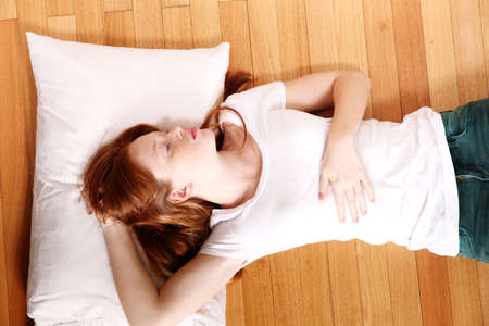 lazyness: A young adult Woman sleeping on the floor.