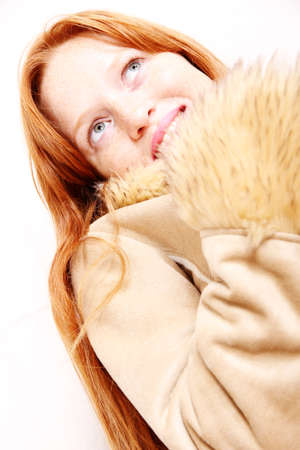 A attractive young, redhead  woman in Winter clothing.   photo