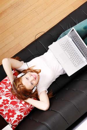 Una giovane donna navigare su Internet con un computer portatile.