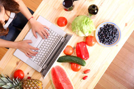 A young woman using a Laptop while cooking  Standard-Bild