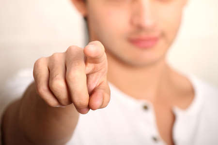 finger tip: A young man pointing at you  Focus on Finger