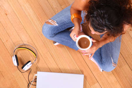 A girl sitting on the floor with a Laptop and some coffee  photo