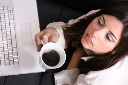 A young, hispanic adult girl watching a Laptop while drinking coffee  photo