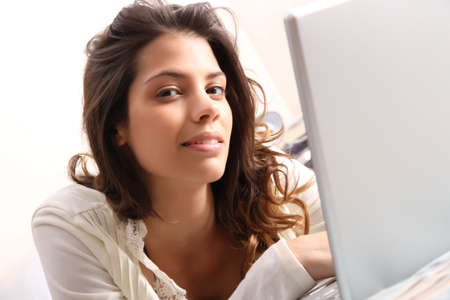 A young girl laying on the bed and surfing on the Internet with a Laptop Stock Photo - 19092765