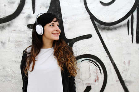youth crime: Girl listening to Music while leaning on a Wall