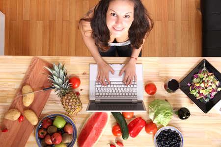 Een jonge vrouw met behulp van een laptop tijdens het koken Stockfoto